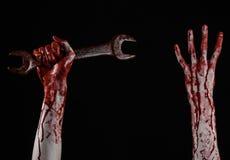 Blodig hand som rymmer en stor skiftnyckel, blodig skiftnyckel, stor tangent, blodigt tema, halloween tema, galen mekaniker, svar Arkivbilder