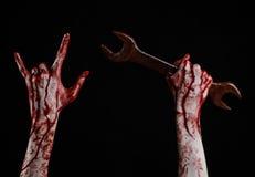 Blodig hand som rymmer en stor skiftnyckel, blodig skiftnyckel, stor tangent, blodigt tema, halloween tema, galen mekaniker, svar Arkivfoto
