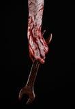 Blodig hand som rymmer en stor skiftnyckel, blodig skiftnyckel, stor tangent, blodigt tema, halloween tema, galen mekaniker, svar Arkivfoton