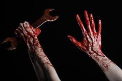 Blodig hand som rymmer en stor skiftnyckel, blodig skiftnyckel, stor tangent, blodigt tema, halloween tema, galen mekaniker, svar Royaltyfria Bilder