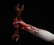 Blodig hand som rymmer en stor skiftnyckel, blodig skiftnyckel, stor tangent, blodigt tema, halloween tema, galen mekaniker, svar Royaltyfri Bild