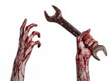 Blodig hand som rymmer en stor skiftnyckel, blodig skiftnyckel, stor tangent, blodigt tema, halloween tema, galen mekaniker, vit  Royaltyfri Bild