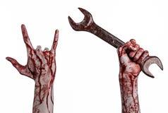 Blodig hand som rymmer en stor skiftnyckel, blodig skiftnyckel, stor tangent, blodigt tema, halloween tema, galen mekaniker, vit  Royaltyfri Foto