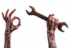 Blodig hand som rymmer en stor skiftnyckel, blodig skiftnyckel, stor tangent, blodigt tema, halloween tema, galen mekaniker, vit  Royaltyfria Foton