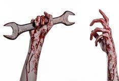 Blodig hand som rymmer en stor skiftnyckel, blodig skiftnyckel, stor tangent, blodigt tema, halloween tema, galen mekaniker, vit  Royaltyfri Fotografi