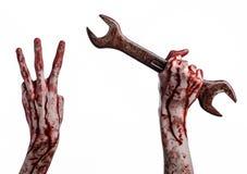Blodig hand som rymmer en stor skiftnyckel, blodig skiftnyckel, stor tangent, blodigt tema, halloween tema, galen mekaniker, vit  Arkivfoto