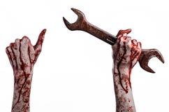 Blodig hand som rymmer en stor skiftnyckel, blodig skiftnyckel, stor tangent, blodigt tema, halloween tema, galen mekaniker, vit  Arkivfoton