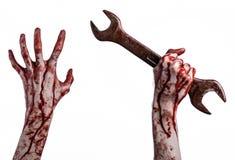 Blodig hand som rymmer en stor skiftnyckel, blodig skiftnyckel, stor tangent, blodigt tema, halloween tema, galen mekaniker, vit  Arkivbild