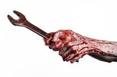 Blodig hand som rymmer en stor skiftnyckel, blodig skiftnyckel, stor tangent, blodigt tema, halloween tema, galen mekaniker, vit  Fotografering för Bildbyråer