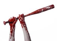 Blodig hand som rymmer ett baseballslagträ, ett blodigt baseballslagträ, slagträ, blodsport, mördare, levande död, halloween tema Arkivfoton