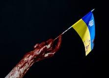 Blodiga händer, flaggan av Ukraina i blodet, revolution i Ukraina, svart bakgrund Fotografering för Bildbyråer