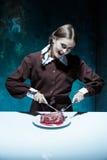 Blodigt allhelgonaaftontema: galen flicka med en kniv, en gaffel och ett kött royaltyfri bild