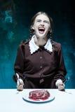 Blodigt allhelgonaaftontema: galen flicka med en kniv, en gaffel och ett kött arkivbild