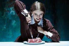 Blodigt allhelgonaaftontema: galen flicka med en kniv, en gaffel och ett kött arkivfoton