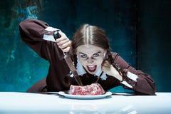 Blodigt allhelgonaaftontema: galen flicka med en kniv, en gaffel och ett kött arkivbilder