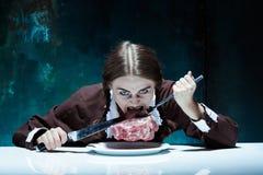 Blodigt allhelgonaaftontema: galen flicka med en kniv, en gaffel och ett kött royaltyfri foto
