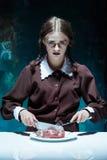 Blodigt allhelgonaaftontema: galen flicka med en kniv, en gaffel och ett kött fotografering för bildbyråer