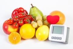 Blodtryckbildskärm och frukter med grönsaker på vit bakgrund, sund livsstil royaltyfri bild