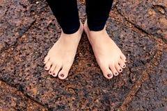 Bloße Füße der Frau auf nasser felsiger Pflasterung Stockfotos