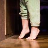 Bloße Füße des Babys vor geschlossener Tür Stockfoto