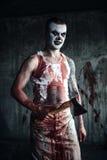 Bloedige clown-maniak met bijl stock foto's