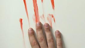 Bloedige hand die onderaan muur, slachtoffer het sterven, contractmoord of moordclose-up glijden stock video