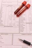 Bloedonderzoekbuis en pen Stock Foto's