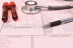Bloedonderzoekbuis en stethoscoop met pen Stock Afbeeldingen