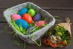 Bloeit de rieten mand van Pasen met gekleurde eieren en een bos van de lente op grijze houten raad Stock Foto's