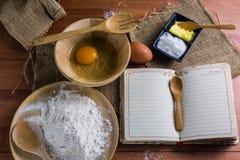Bloem, boter, suiker, eieren, Boeknota's, de Bruine houten bevloering Royalty-vrije Stock Foto
