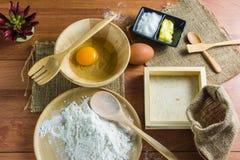Bloem, boter, suiker, eieren, cake met een apparaat op een lijst De Bruine houten bevloering royalty-vrije stock foto's