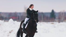 Bloem in de sneeuw Een jonge vrouw met lang haar die een paard in een dorp berijden stock videobeelden