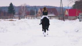 Bloem in de sneeuw Een vrouw die een paard in een dorp berijden stock video
