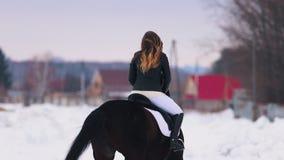 Bloem in de sneeuw Een vrouw met rode lippenstift die een paard in een dorp berijden stock video