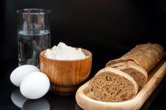 Bloem, eieren, glas water met verse gesneden baguette op zwarte Royalty-vrije Stock Foto's