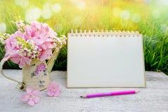 Bloem op houten lijst in zachte pastelkleurtoon van het groene gras van de bokehaard, met inbegrip van blanco paginakalender, de  Stock Afbeeldingen