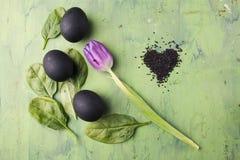 Bloem van tulp met zwart die eieren en sesamhart op de groene achtergrond wordt gevormd Concept het gezonde eten Stock Foto's