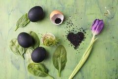 Bloem van tulp met zwart die eieren en sesamhart op de groene achtergrond wordt gevormd Concept het gezonde eten Royalty-vrije Stock Afbeelding