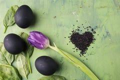 Bloem van tulp met zwart die eieren en sesamhart op de groene achtergrond wordt gevormd Concept het gezonde eten Stock Afbeelding
