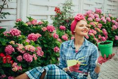 Bloem zorg en het water geven gronden en meststoffen Serrebloemen gelukkige vrouwentuinman met bloemen hydrangea royalty-vrije stock afbeeldingen
