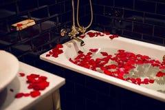 Bloemblaadjes van rode rozen in een witte badkamers met zwarte tegels royalty-vrije stock afbeelding