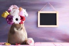 Bloemboeket in een jutezak en een bord Royalty-vrije Stock Afbeeldingen