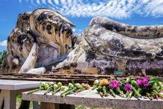Bloemen aan doende leunen Boedha van Wat Lokaya Sutha, Thailand worden aangeboden dat Stock Foto's