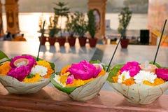 Bloemen in bladeren klaar voor een puja bij de tempel bij de rivier Ganges stock foto