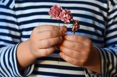 Bloemen in de handen van een kind Stock Afbeeldingen