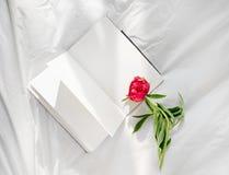 Bloemen die op open boek in bed blijven Romantische goedemorgen Hoogste mening stock fotografie
