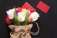 Bloemen in een jutezak en een berichtkaart Stock Foto's
