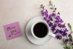 Bloemen, een kop thee en een nota stock foto