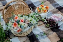 Bloemen in een mand op plaid Stock Fotografie
