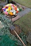 Bloemen en bloesems en schop met grond voor begrafenis royalty-vrije stock afbeeldingen